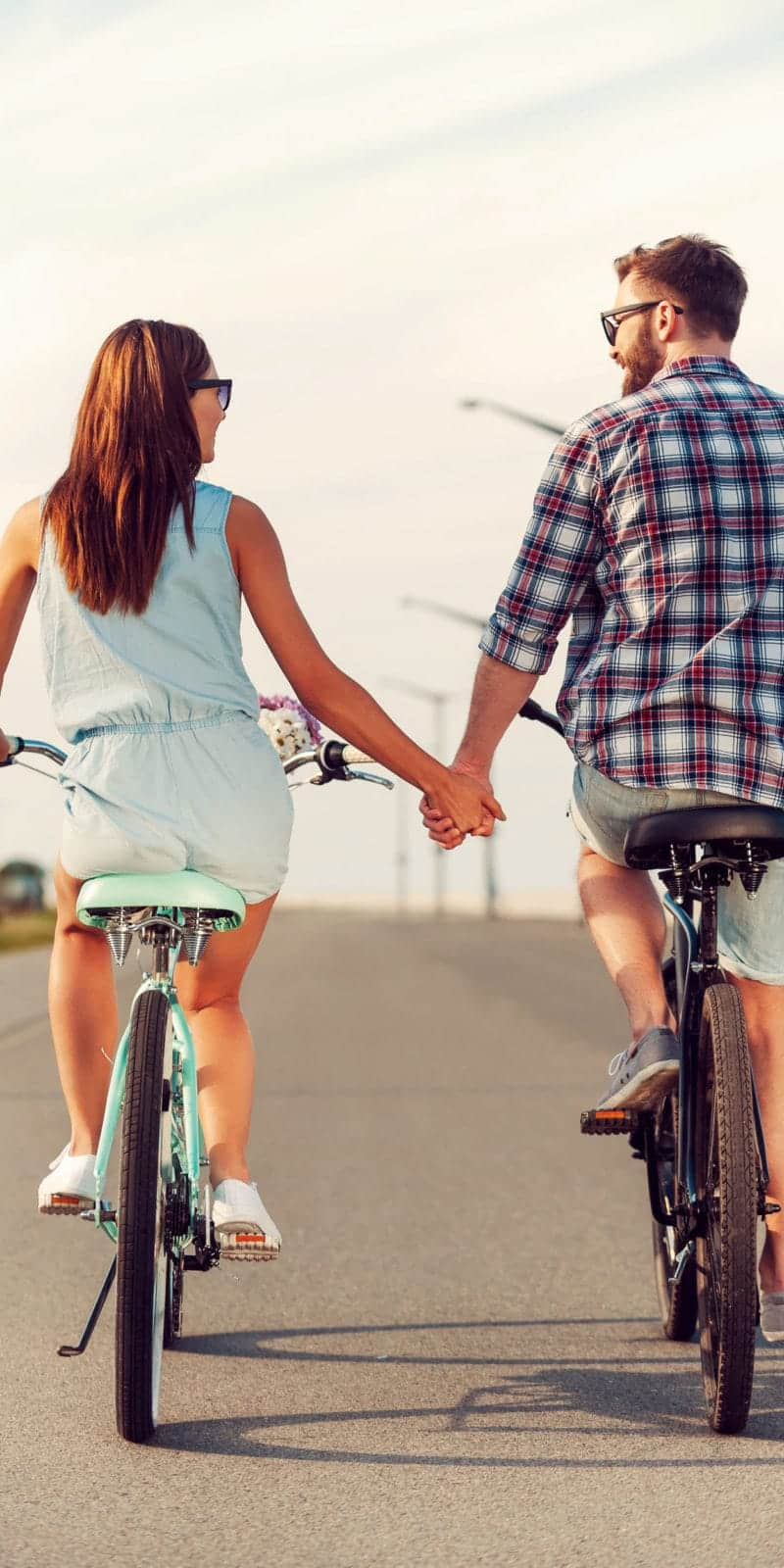 rear view of young couple holding hands while riding on bicycles along the road